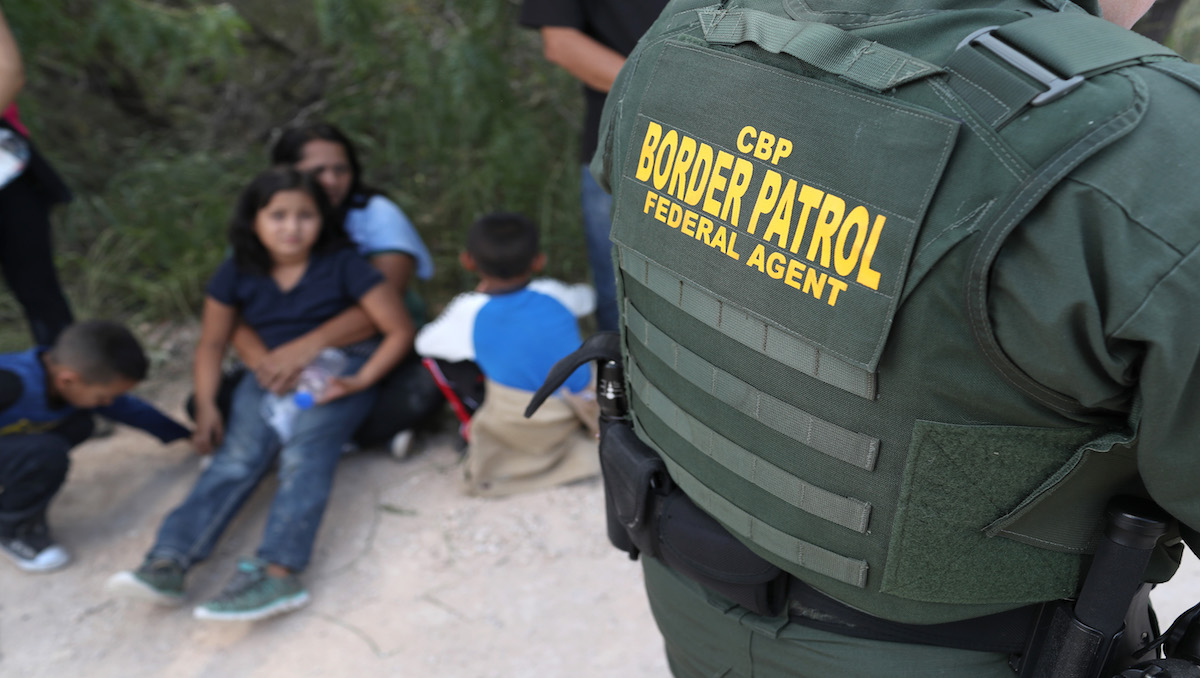Central American asylum seekers wait as U.S. Border Patrol agents take them into custody on June 12, 2018 near McAllen, Texas. The families were then sent to a U.S. Customs and Border Protection (CBP) processing center for possible separation.