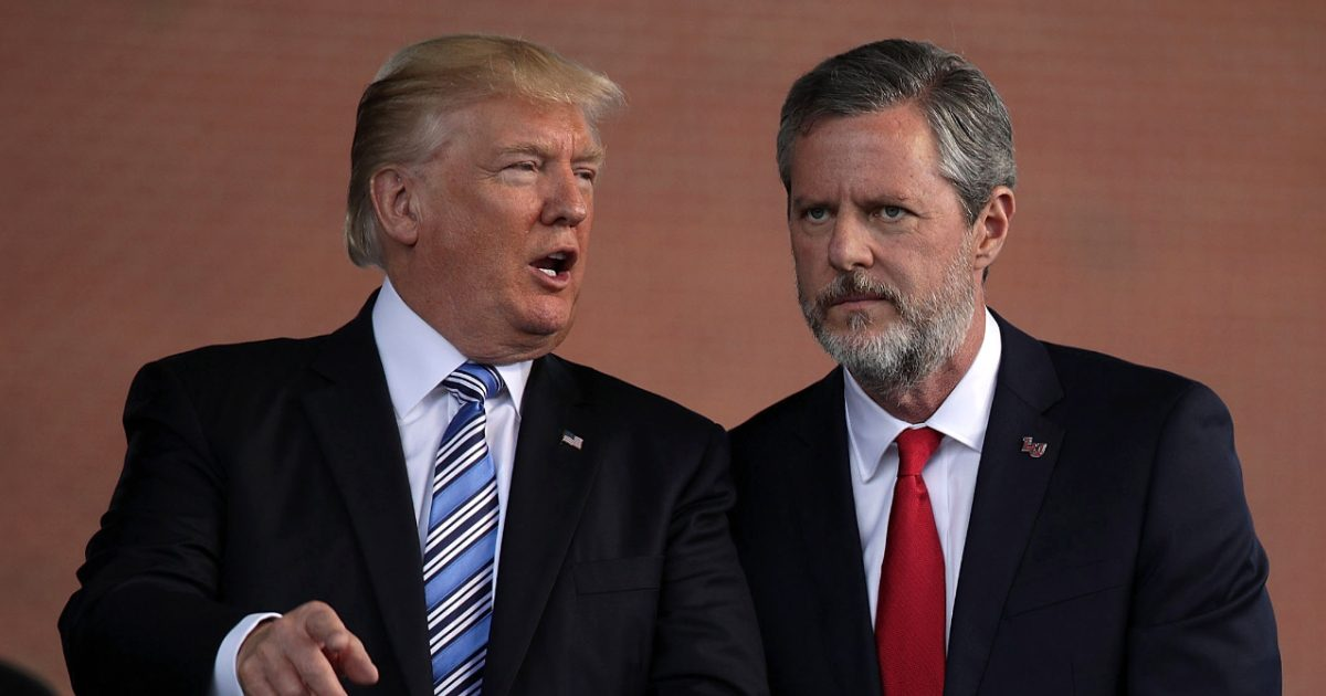 President Donald Trump and Jerry Falwell, Jr. huddle close together on stage at Liberty University in 2017.