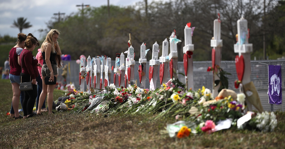 People visit a makeshift memorial setup in front of Marjory Stoneman Douglas High School on February 19, 2018 in Parkland, Florida.