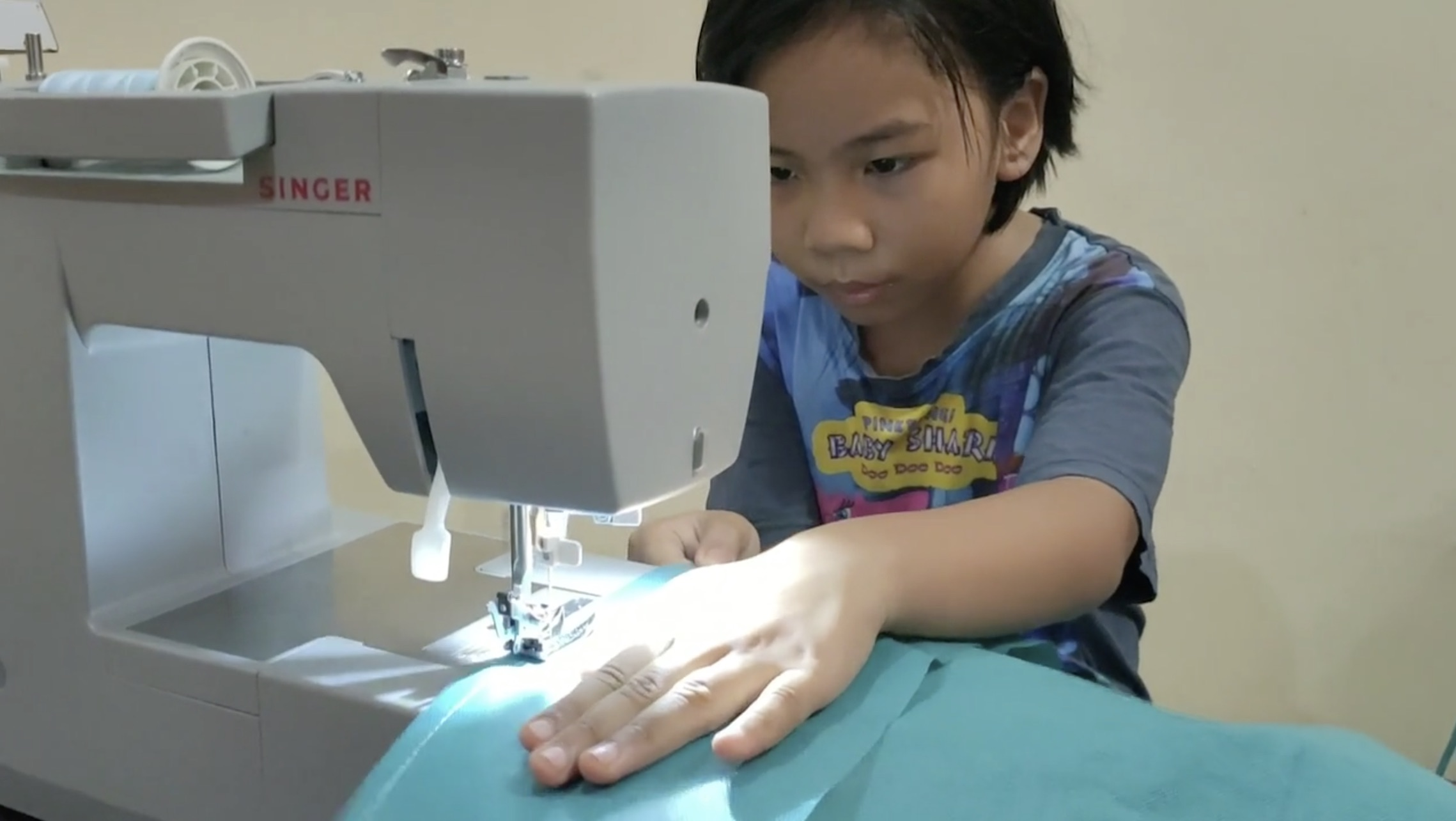 Malaysian girl sewing ppe