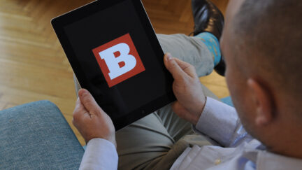 A man holds an iPad with the Breitbart logo on it's screen on November 10, 2017. (Photo by Jaap Arriens/NurPhoto via Getty Images)