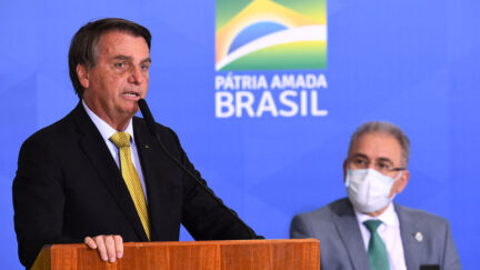Brazilian President Jair Bolsonaro (L) speaks near Health Minister Marcelo Queiroga