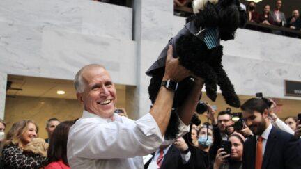 tillis holds up his dog mitch